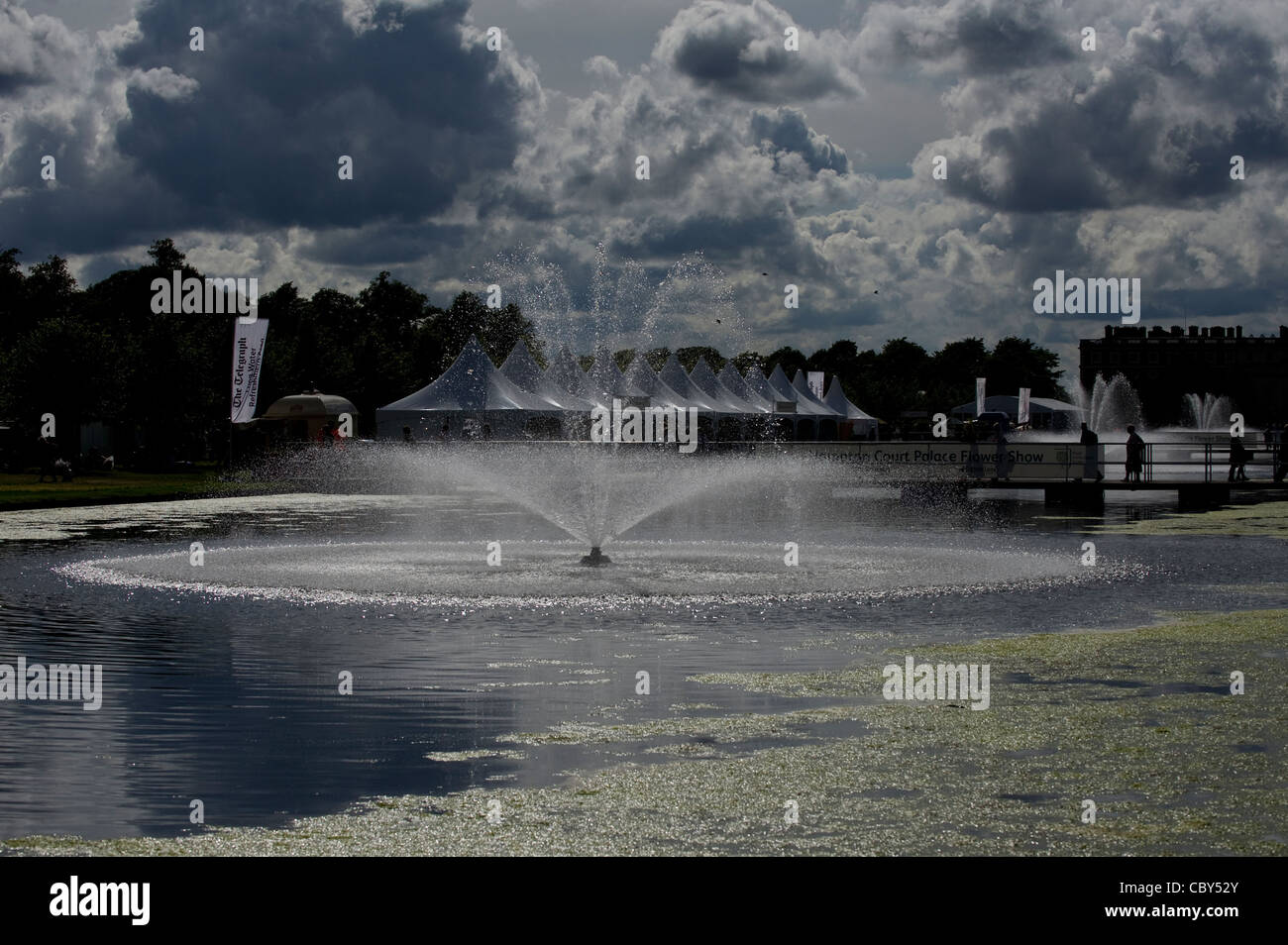 Ornamental Fountain and Lakes at Hampton Court during the Royal Hampton Court Flower Show with marquees and clouds Stock Photo