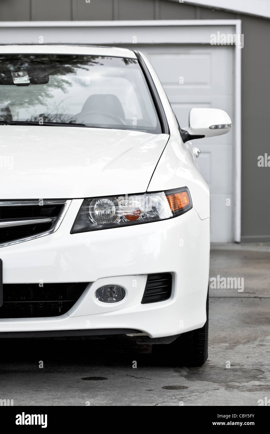 White sport sedan car, parked in driveway - Stock Image