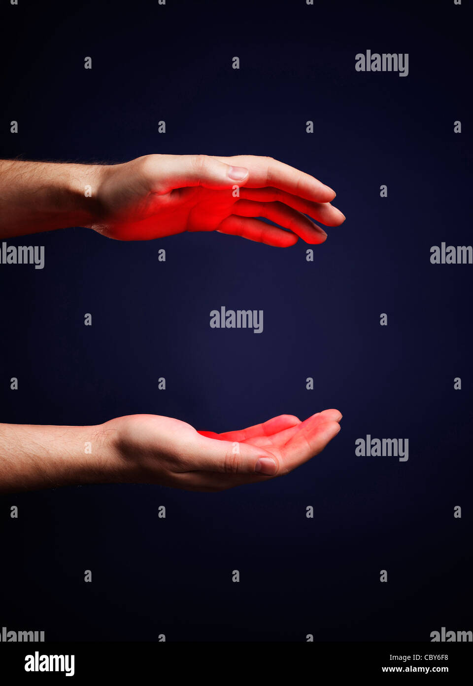 Hands of a man with a red glow. - Stock Image