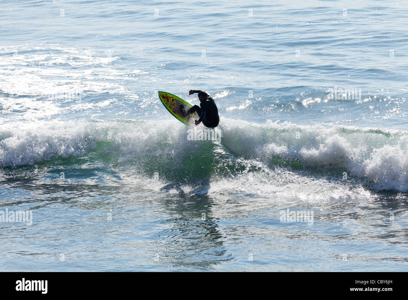 Surfer catches air on Pacific Ocean near Waddell Creek along highway one in California - Stock Image