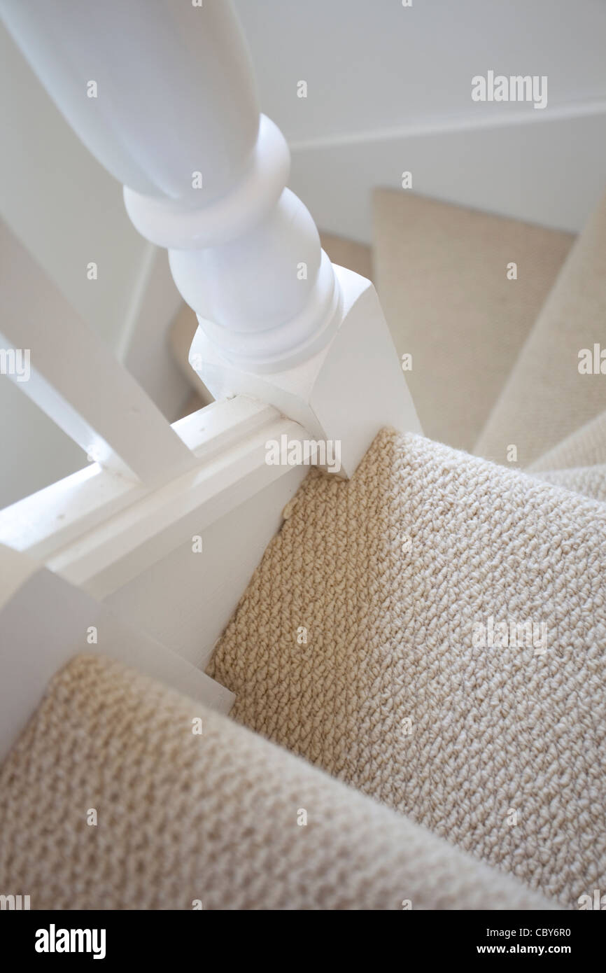 looking down stairs with carpet and white painted wood work - Stock Image