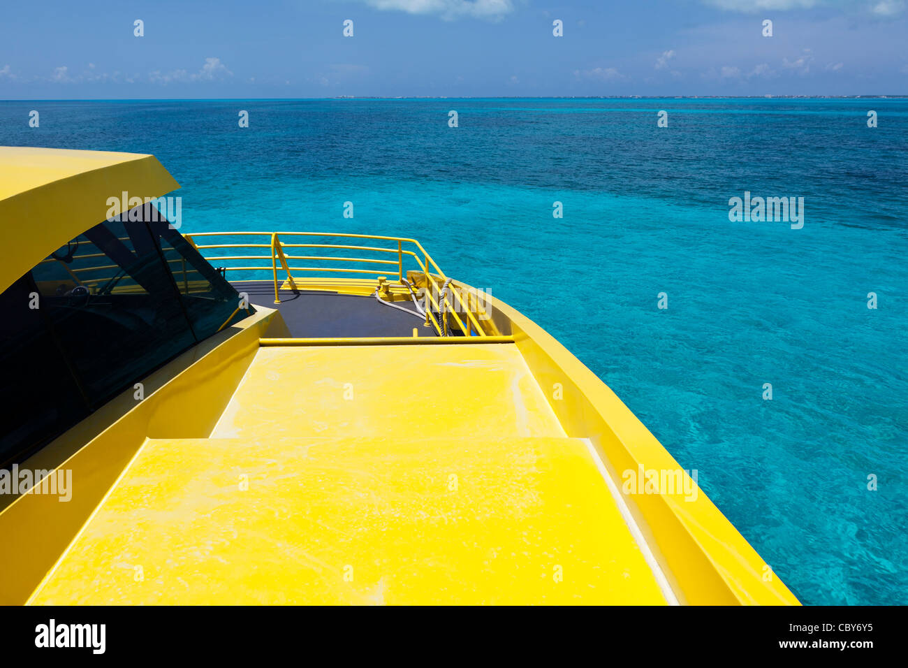 View of the ocean from the deck of a bright yellow boat - Stock Image