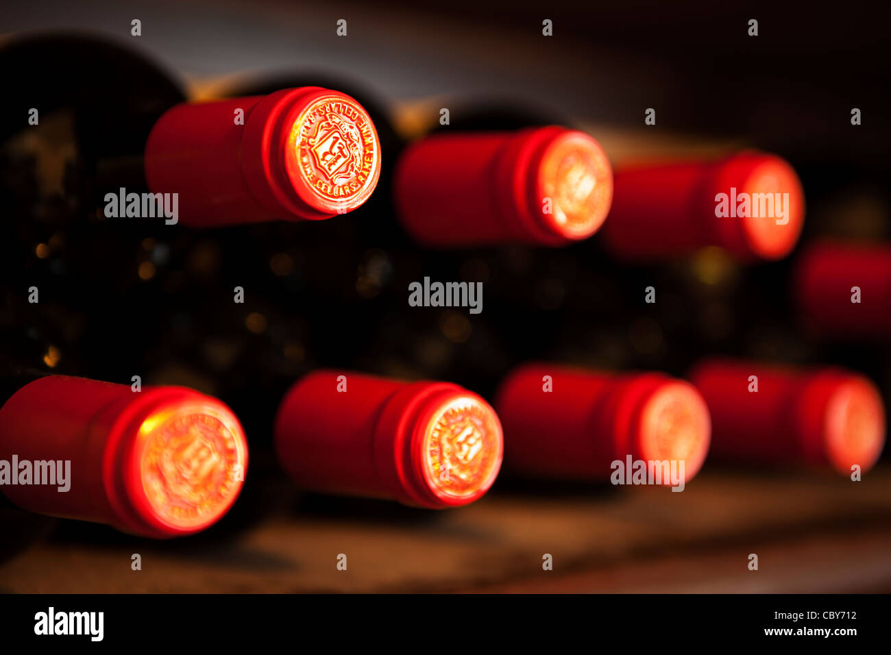 Abstract of red wine bottle tops on a wine rack - Stock Image