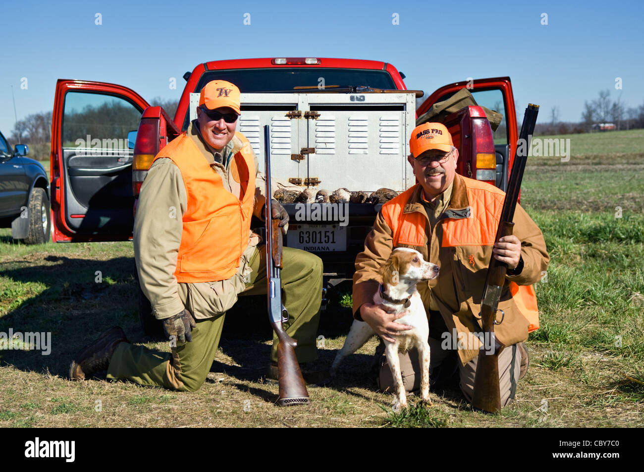 Two Upland Bird Hunters Posing Behind Truck with Shotguns, Quail and English Setter - Stock Image