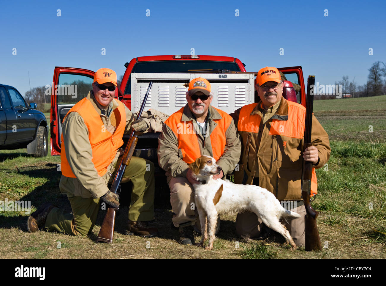 Three Upland Bird Hunters Posing Behind Truck with Shotguns, Quail and English Setter - Stock Image