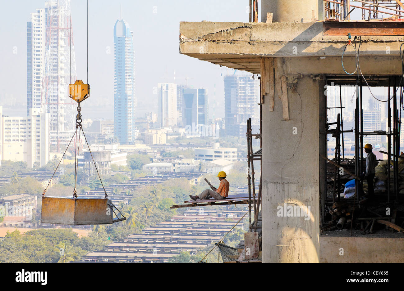 Workman sat on an overhanging board at work on the 17th floor of high rise block, no harness or safety gear - Stock Image