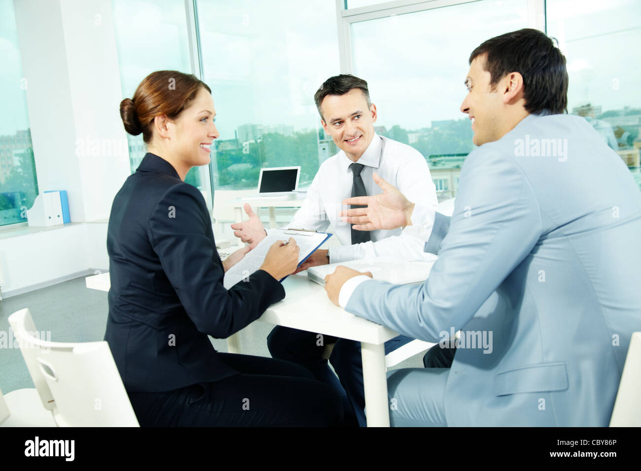 Portrait of friendly professionals planning work in office - Stock Image