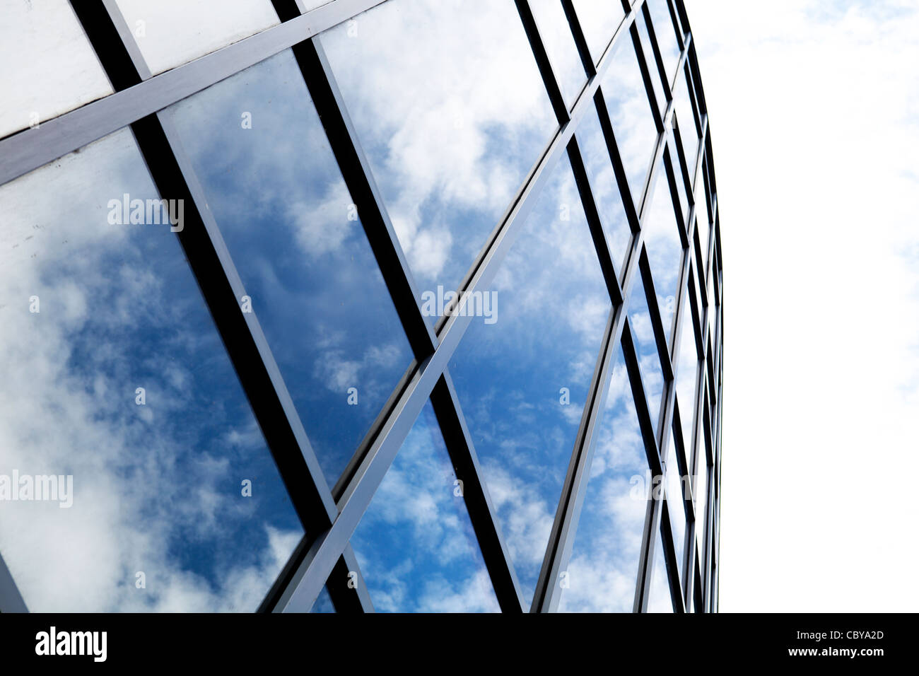 Modern commercial building with sky reflected in the glass windows Stock Photo