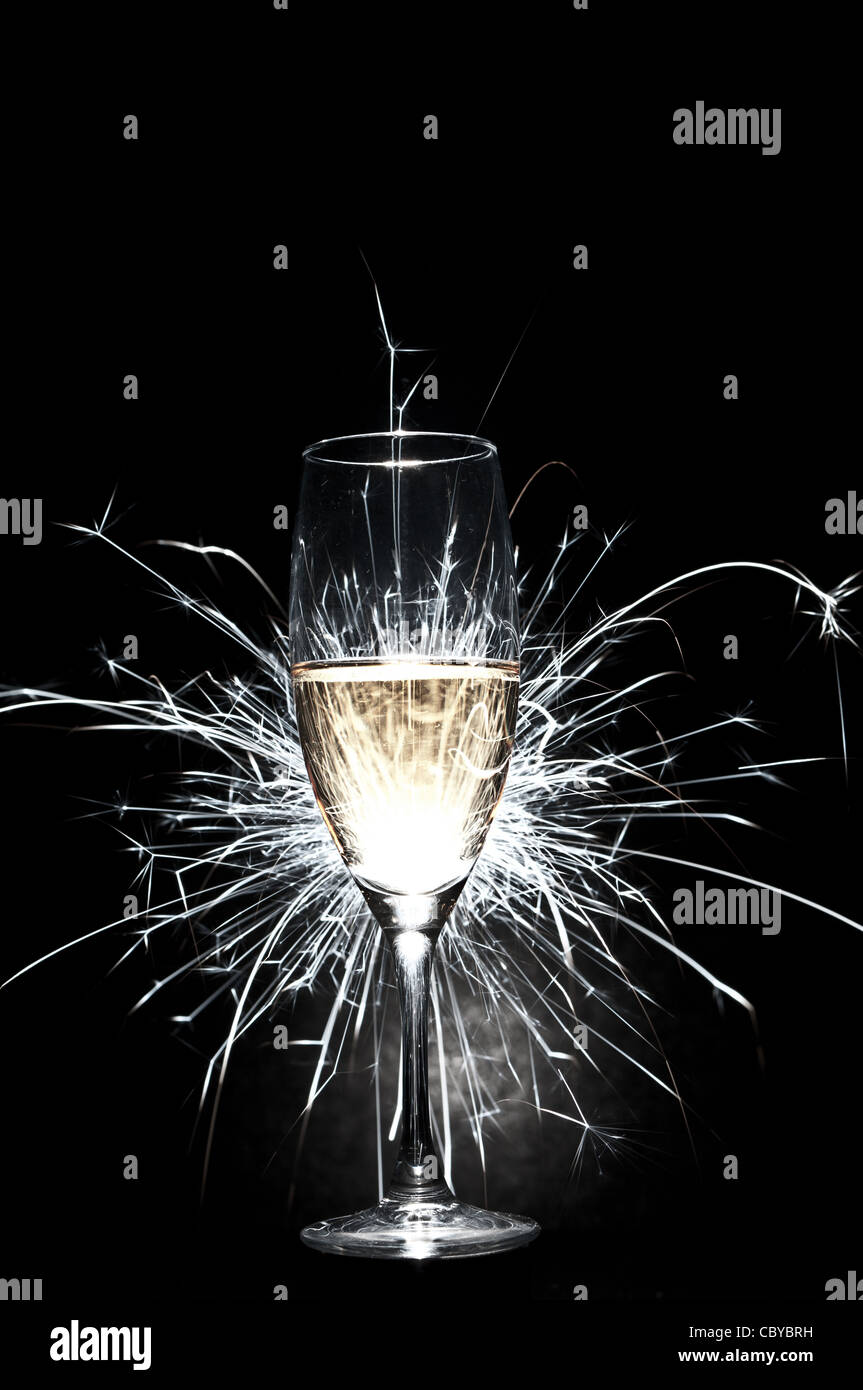 glass of champagne with fire works - Stock Image