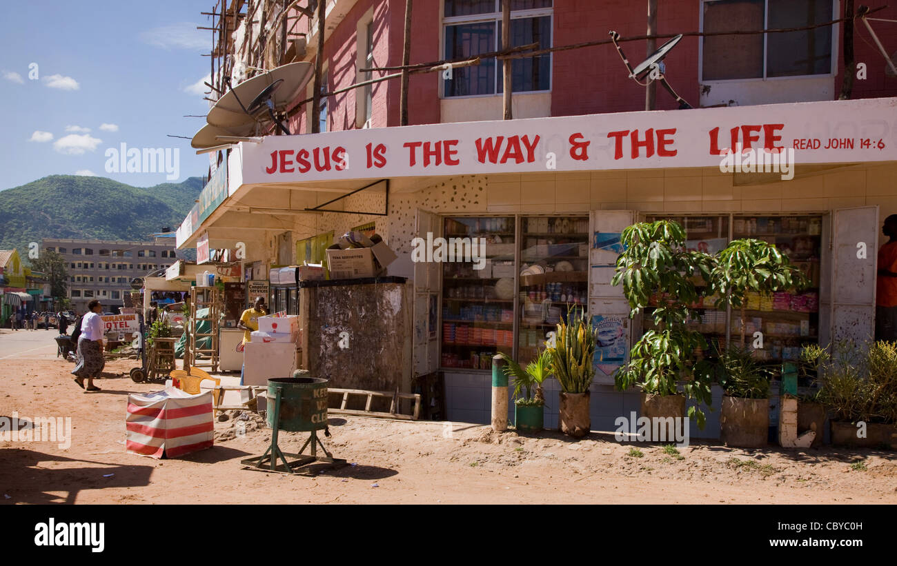 Religious slogan on an arcade of shops in the bustling town of Voi in southern Kenya Stock Photo