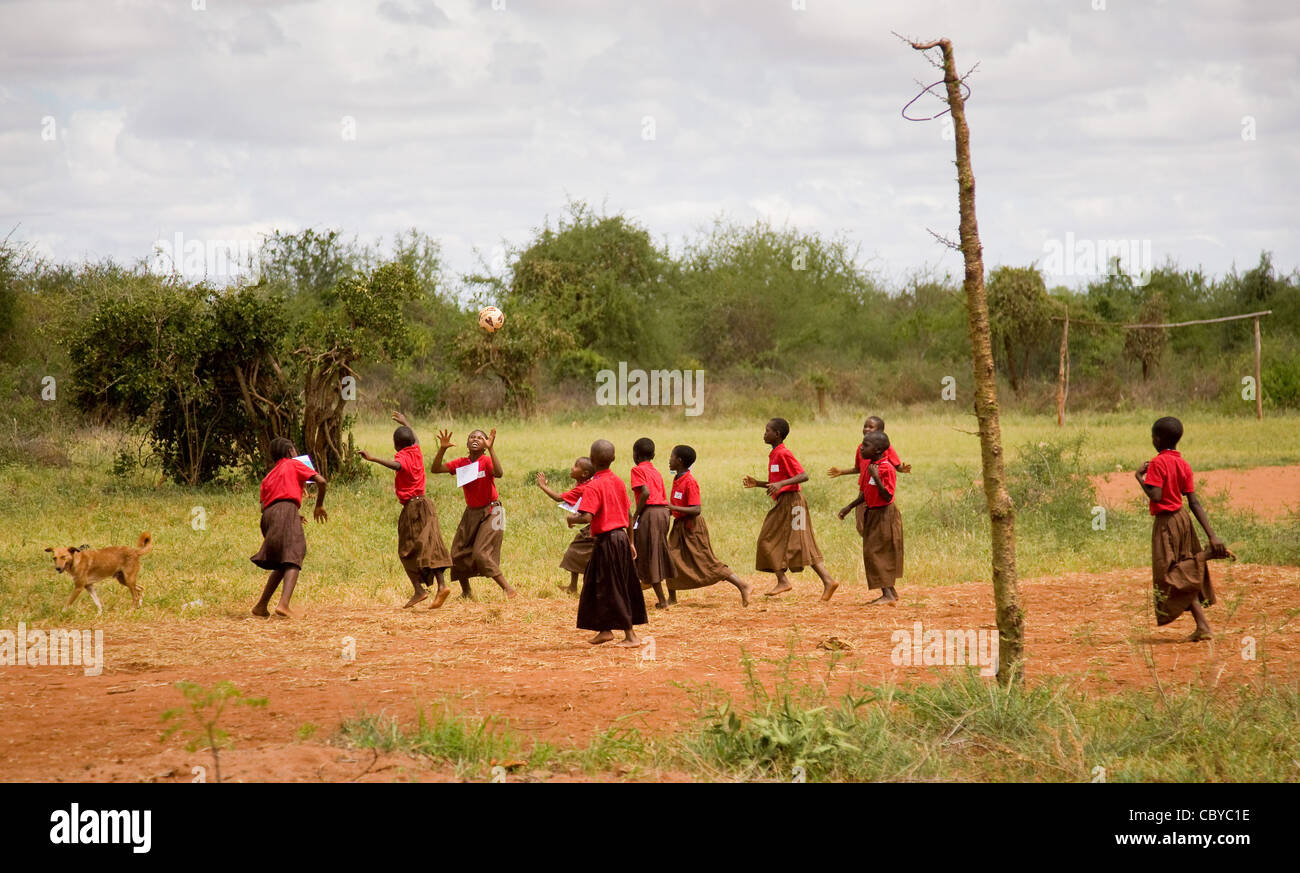Teenage children playing a game of netball on a school playing field near Voi in southern Kenya while a dog looks - Stock Image
