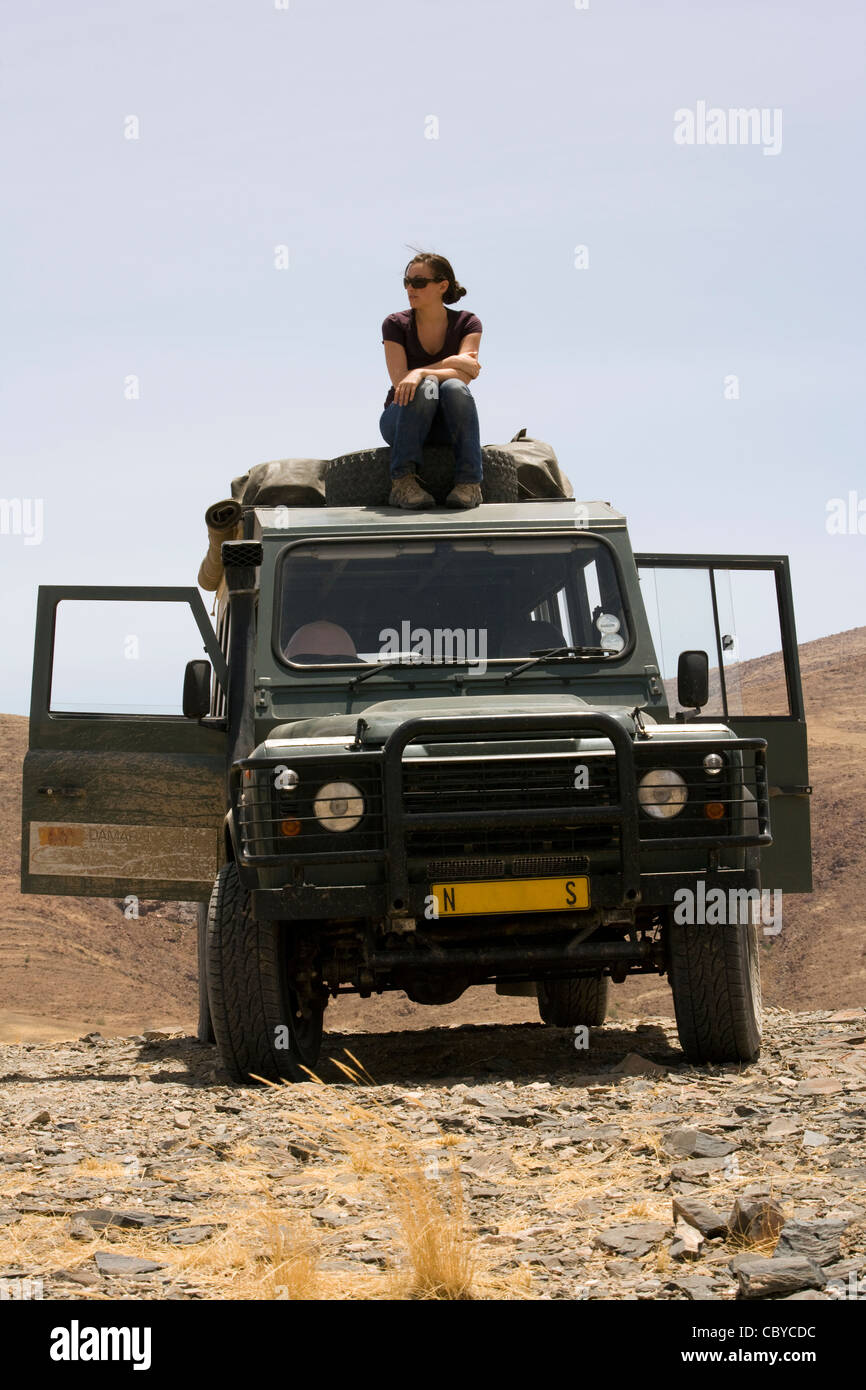 Young woman sitting on top of safari vehicle - Purros Conservancy - Kaokoland, Kunene Region, Namibia, Africa - Stock Image