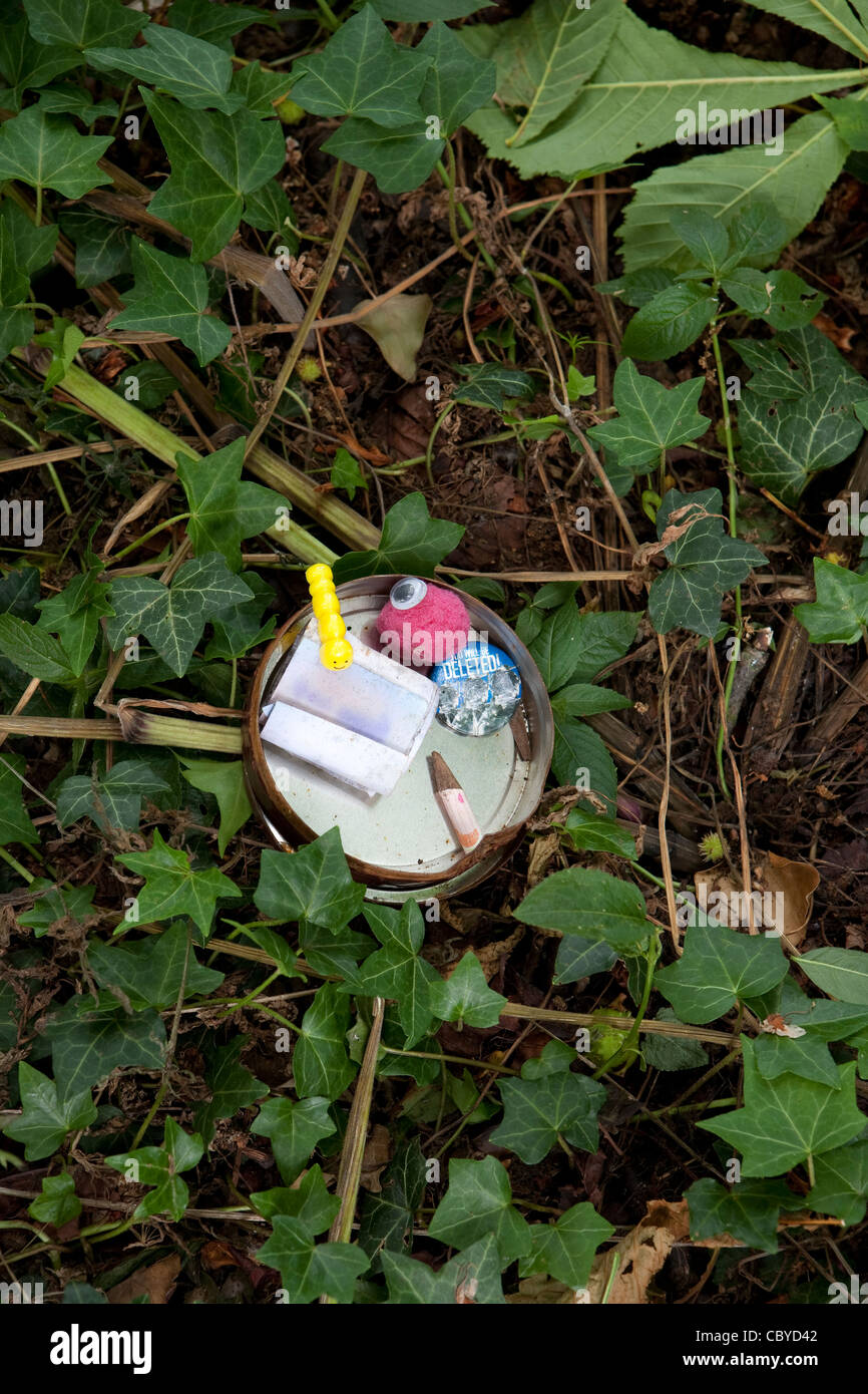 Small open Geocache tin showing its contents - Stock Image