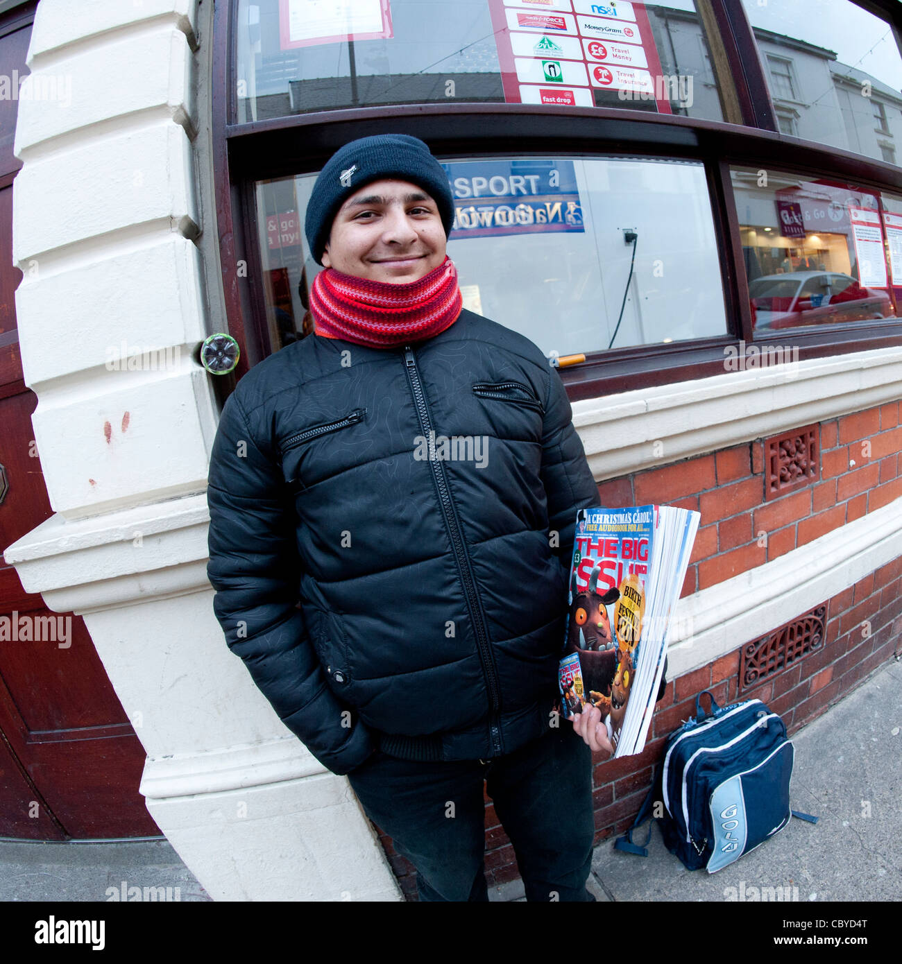 A homeless man selling copies of The Big Issue magazine, Christmas Eve, UK - Stock Image
