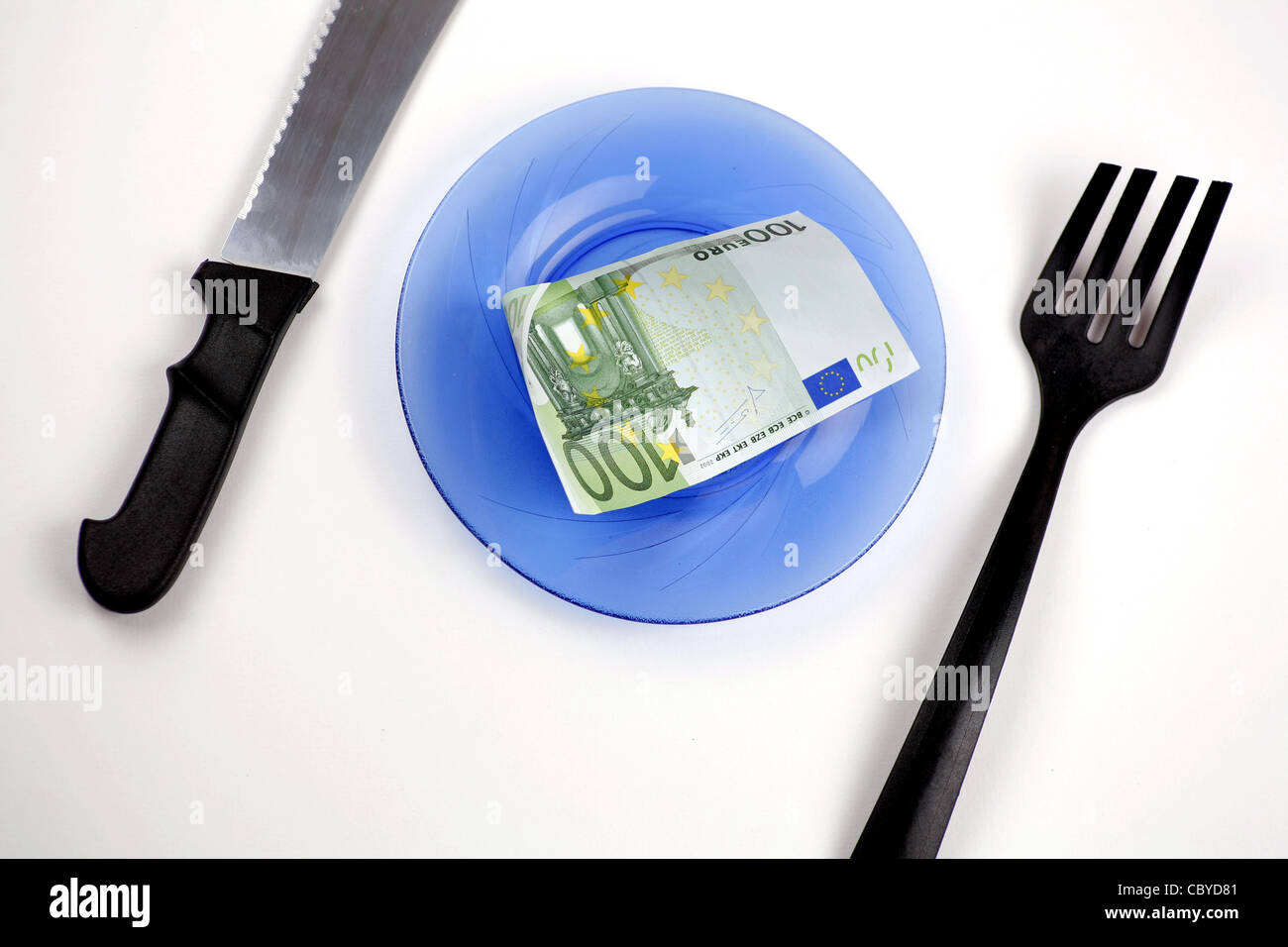 One hundred euro bill on a plate, with knife and fork Stock Photo