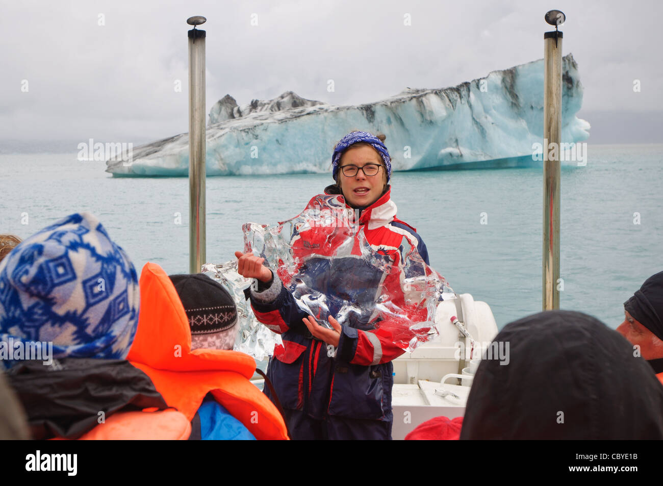 A guide explains glacial ice onboard a tour of Glacier Lagoon, Iceland. - Stock Image