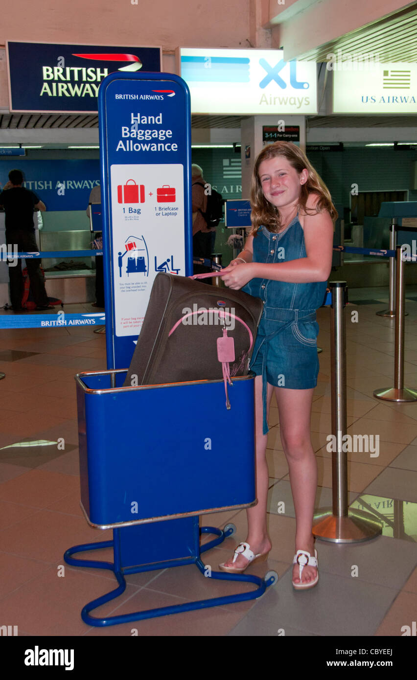 Young Girl Checking Size of Hand Baggage at Airport - Stock Image