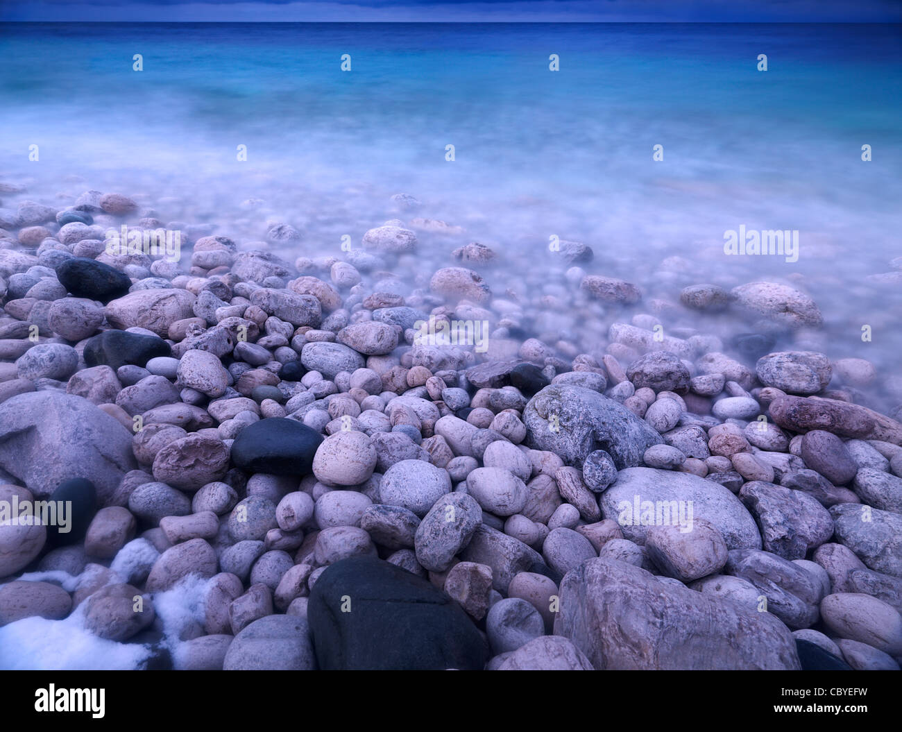 Pebbles on a shore of Georgian Bay. Wintertime scenic landscape. Bruce Peninsula National Park, Ontario, Canada. - Stock Image