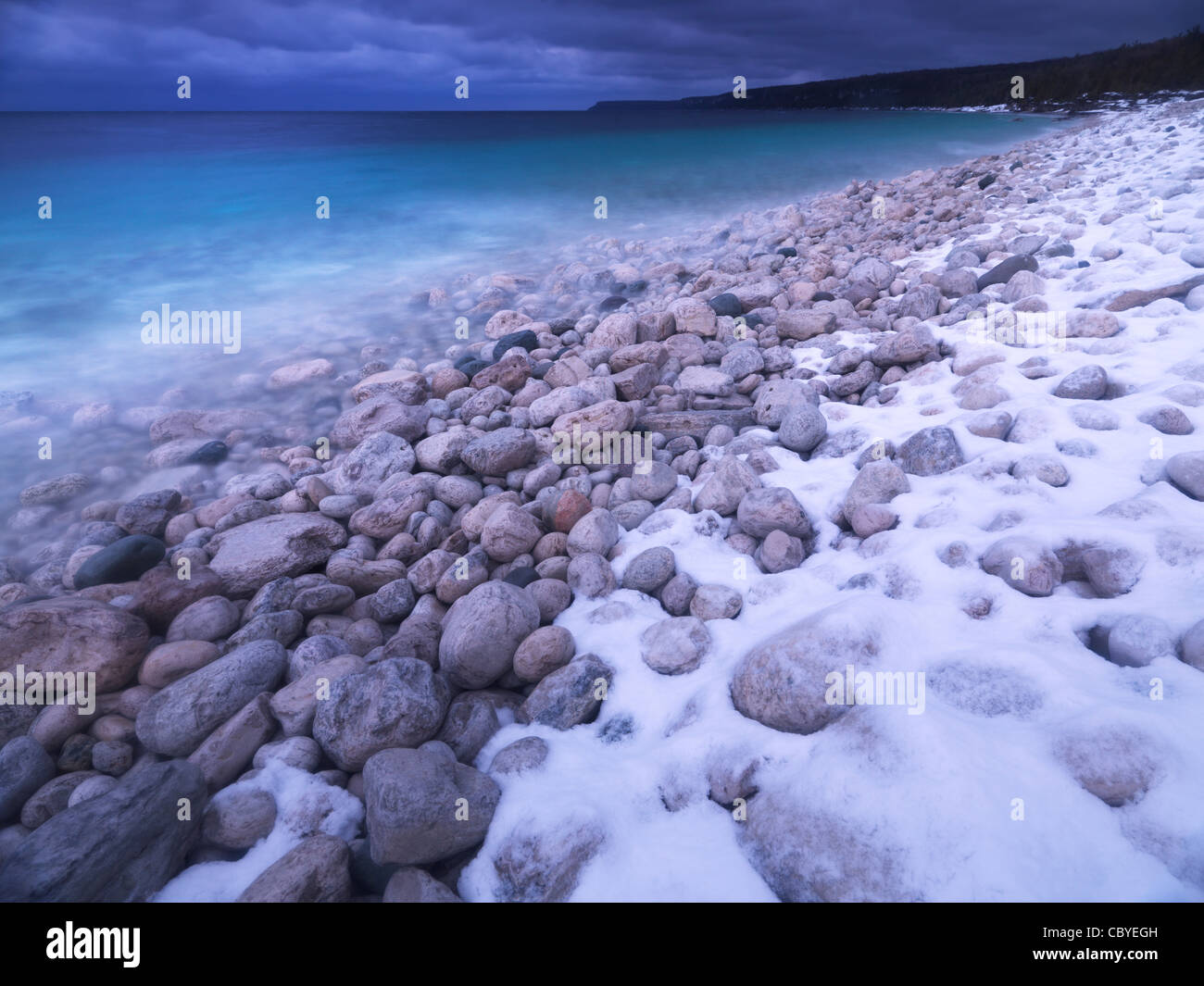 Pebbles on a shore of Georgian Bay covered with light snow. Wintertime scenic landscape. Bruce Peninsula National - Stock Image