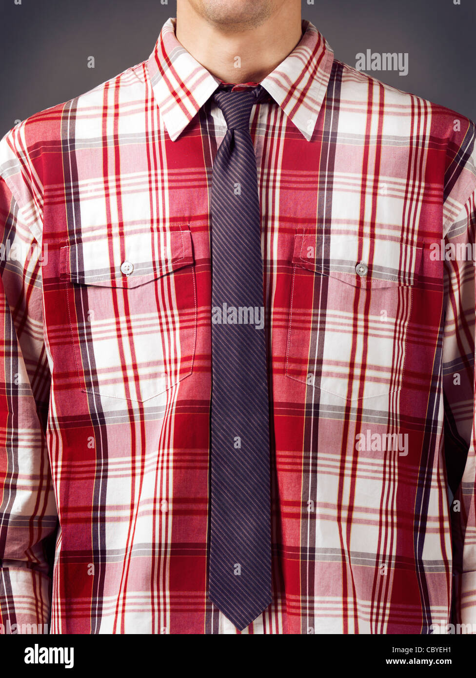 Closeup of a man wearing fancy red tartan shirt with a skinny stripy necktie. - Stock Image