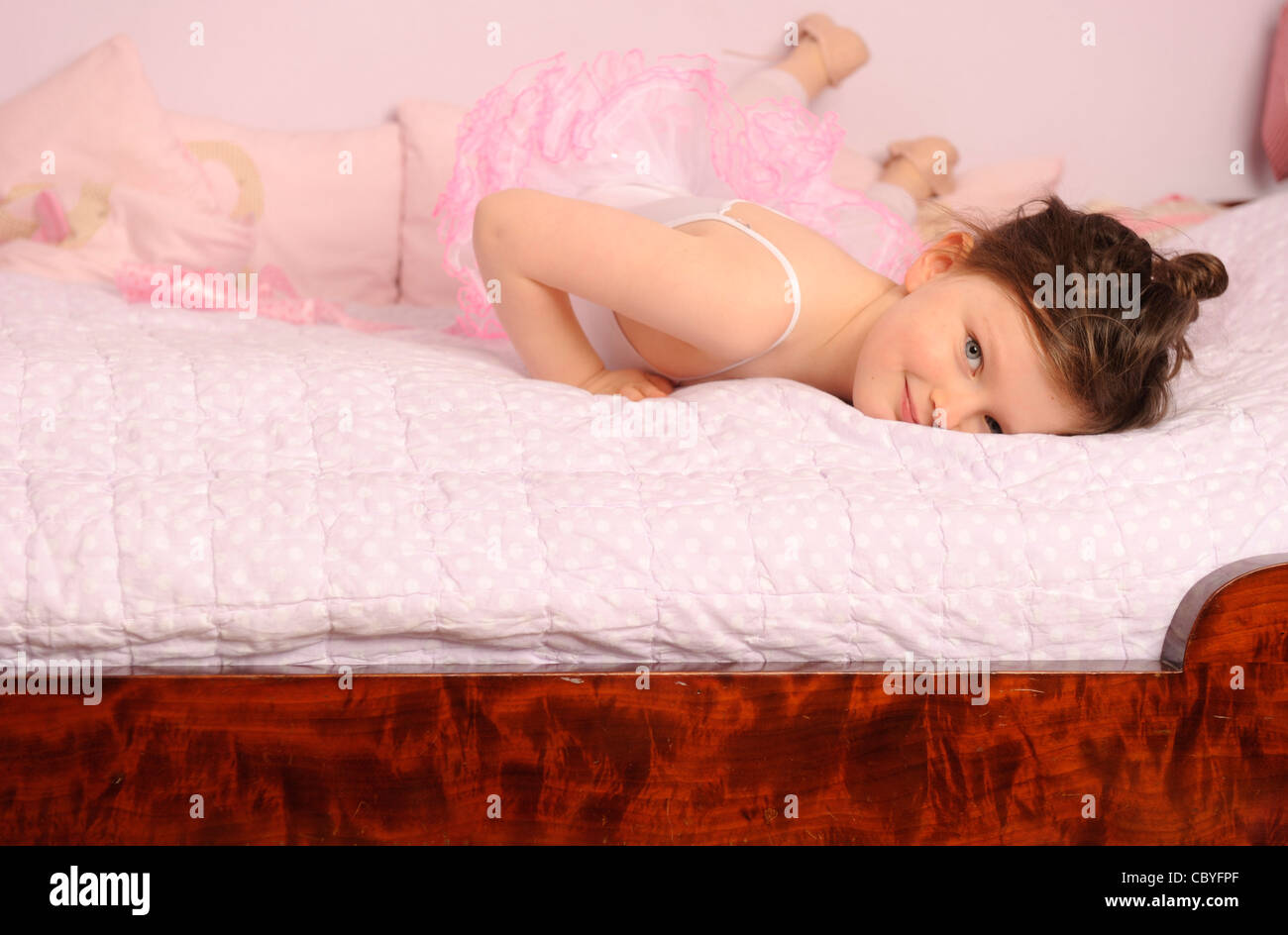 Girl of five years posing in her ballet outfit on her bed. - Stock Image
