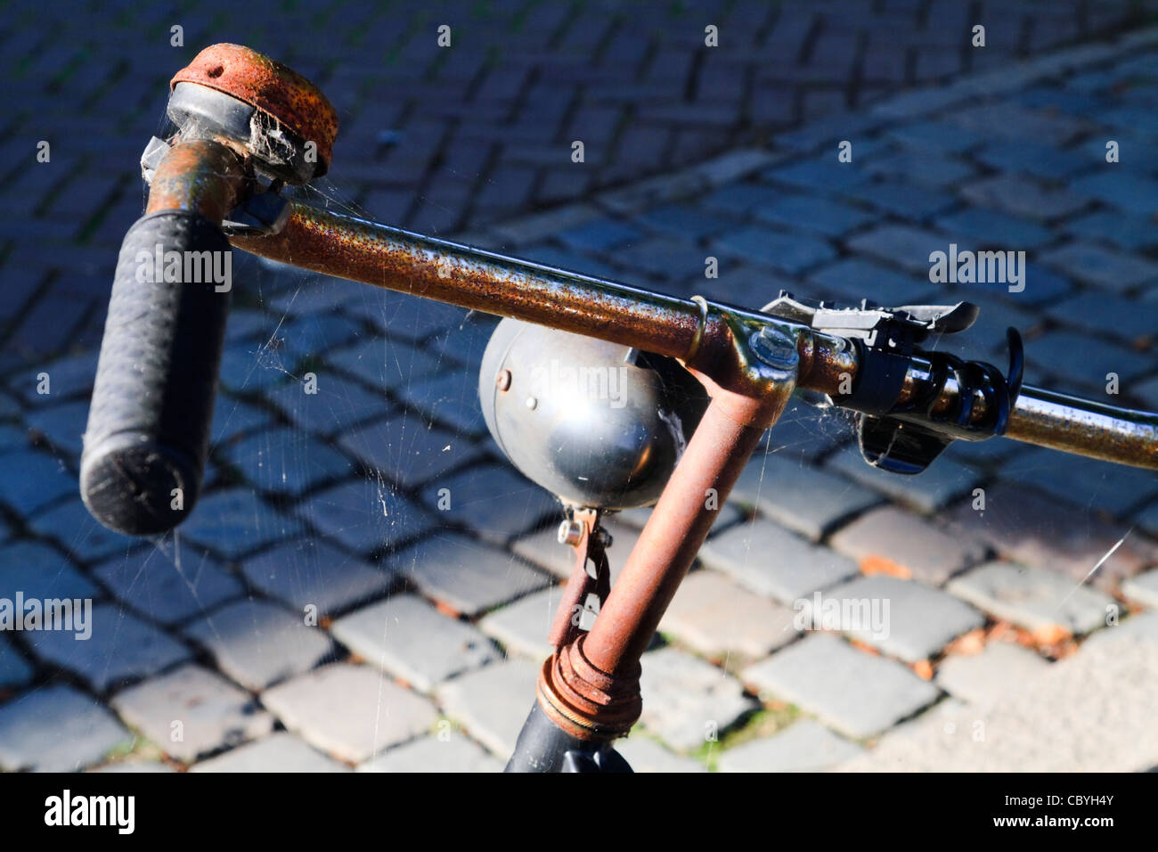 An old rusty dumped bicycle on a cobbled street - Stock Image