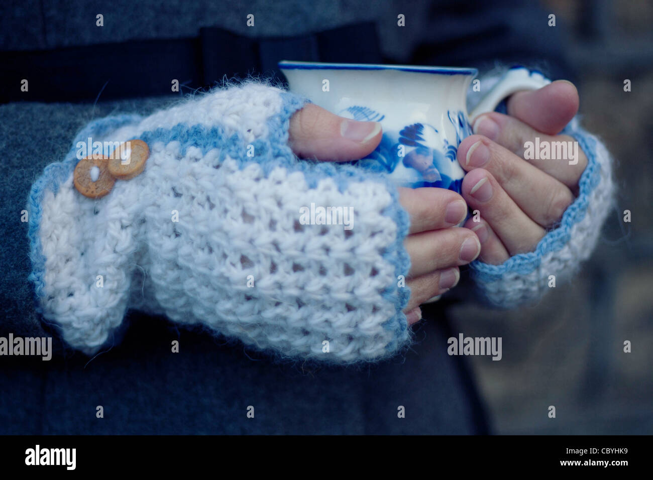 Crocheted mittens with wooden buttons and a white/blue cup - Stock Image