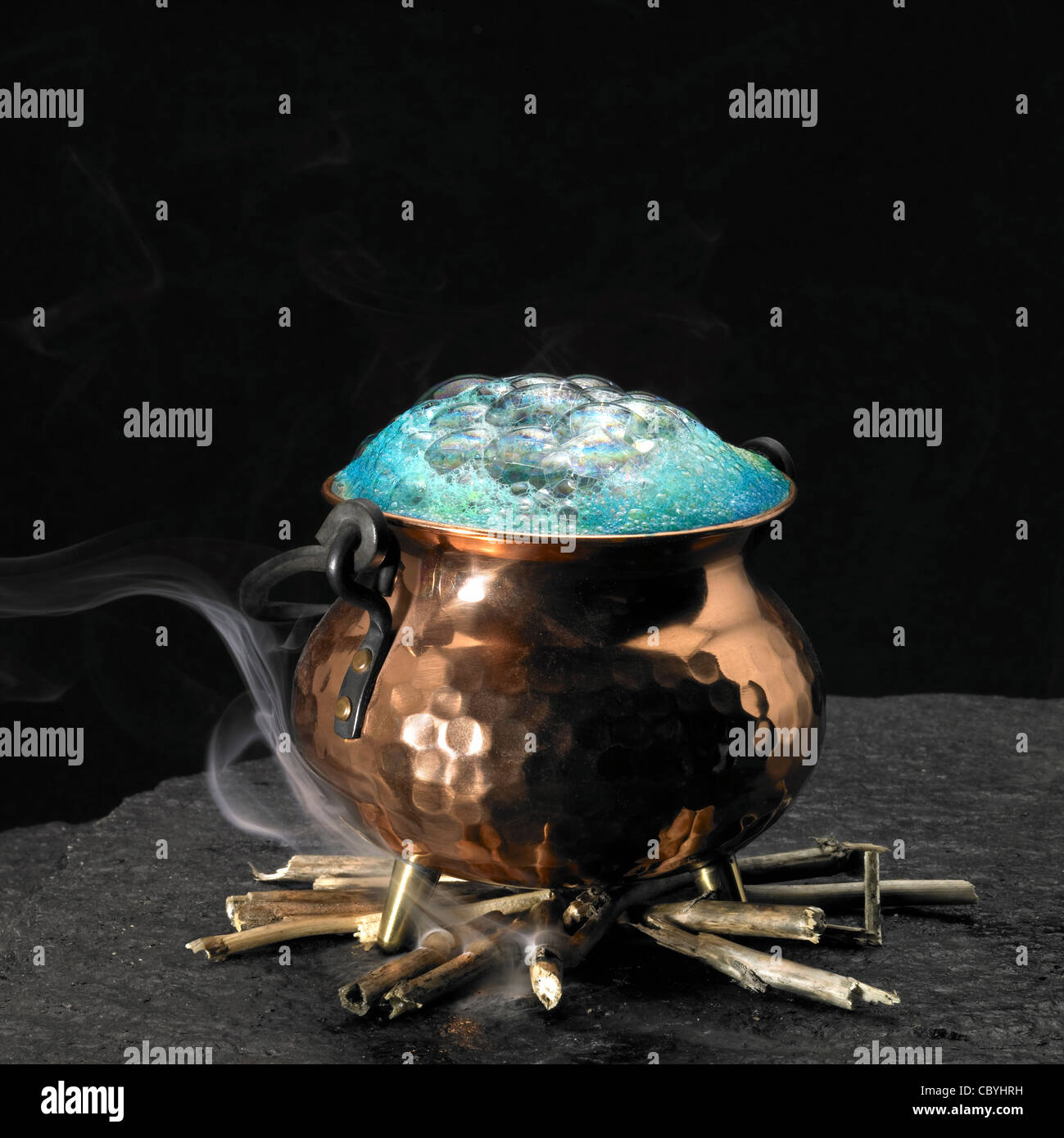 symbolic picture with spumous potion and copper cauldron on a fireplace - Stock Image