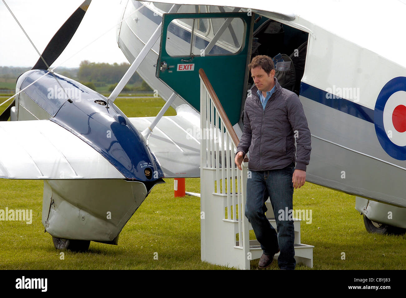 Country file is a UK TV programme. One of the presenters is Matt Baker, seen during filming at Cotswold Airport, - Stock Image