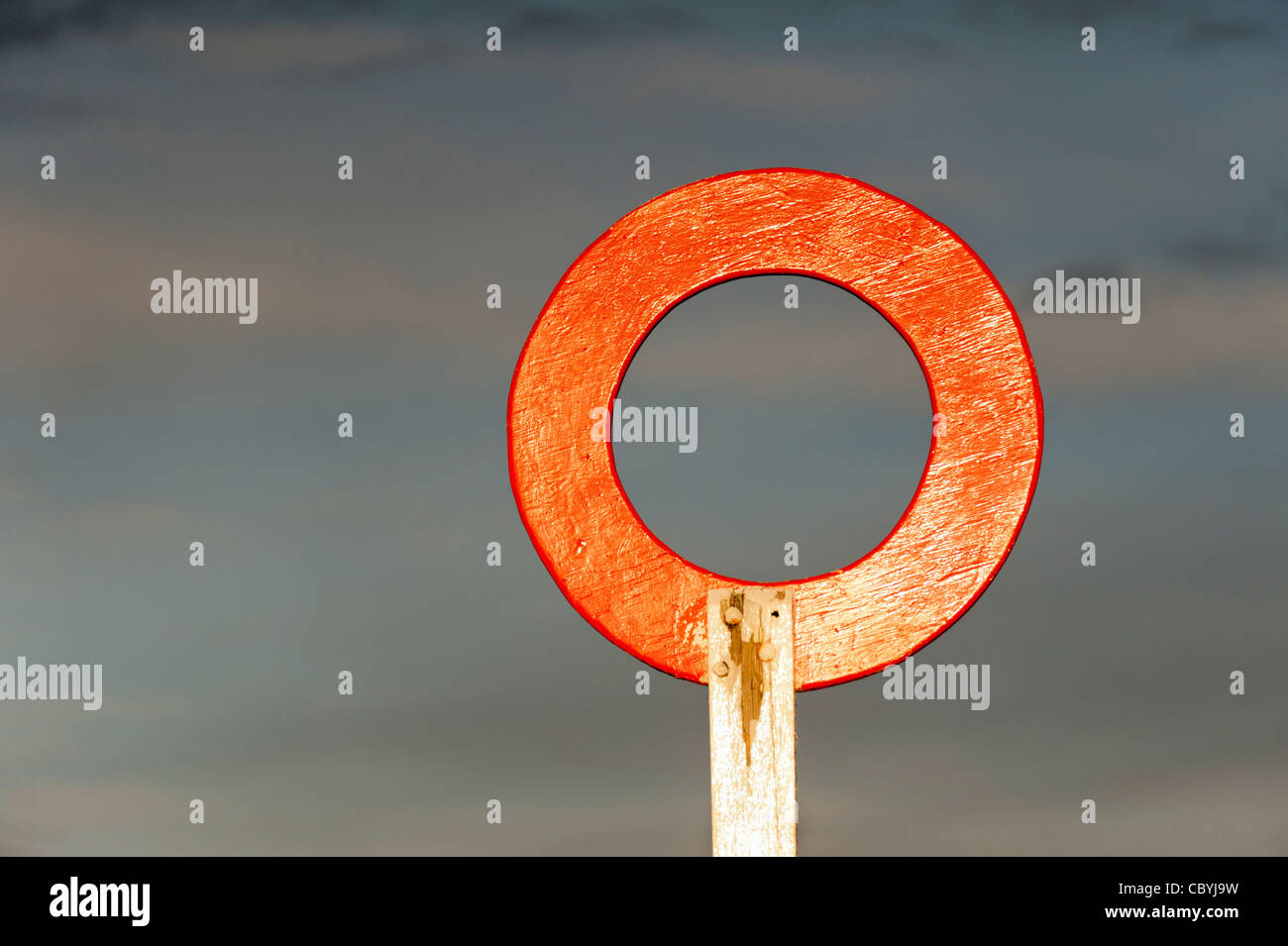 Red finishing post circle in sunshine against a stormy sky - Stock Image