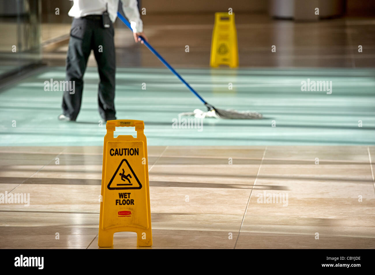 Office cleaner using mop - Stock Image