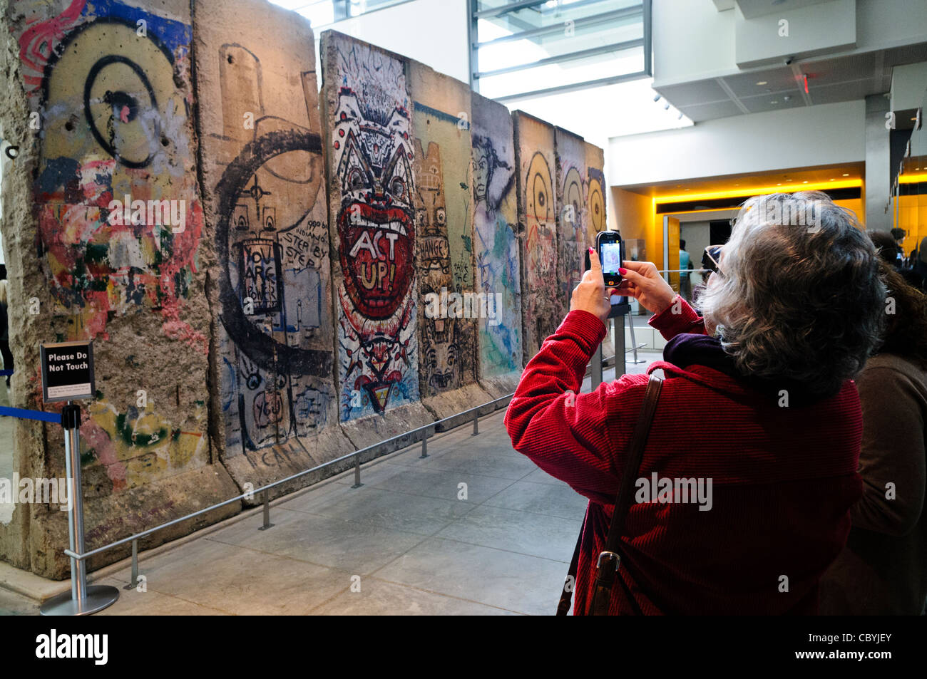 WASHINGTON DC, USA - Tourists use a smartphone to take a photo of the large section of the Berlin Wall at the Newseum - Stock Image