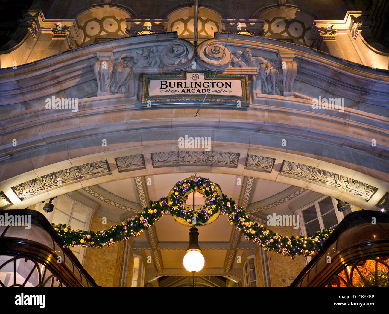 Burlington luxury shopping arcade entrance in Piccadilly with traditional Christmas lights and decorations at dusk - Stock Image