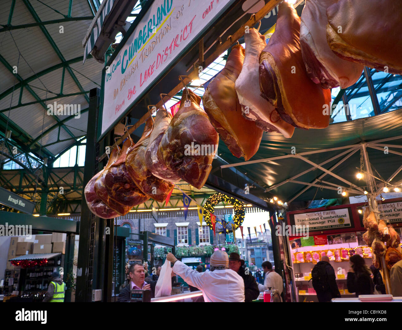 Legs of ham air curing on display for sale at Borough Market  butchers stall Southwark London UK - Stock Image