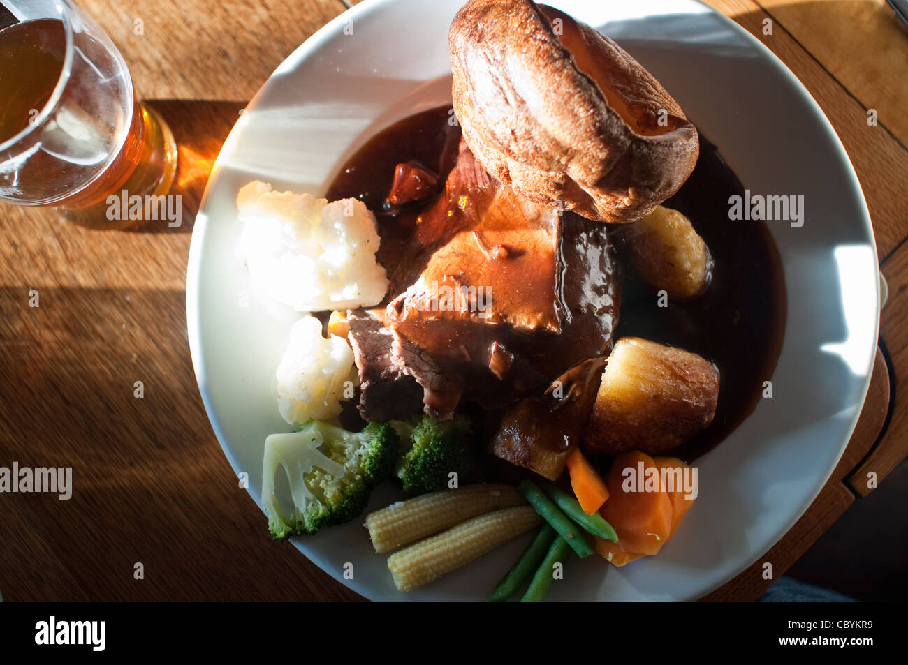 A typical roast beef Sunday lunch with yorkshire pudding, vegetables, gravy, and a pint of ale, in a pub in Northumberland, - Stock Image