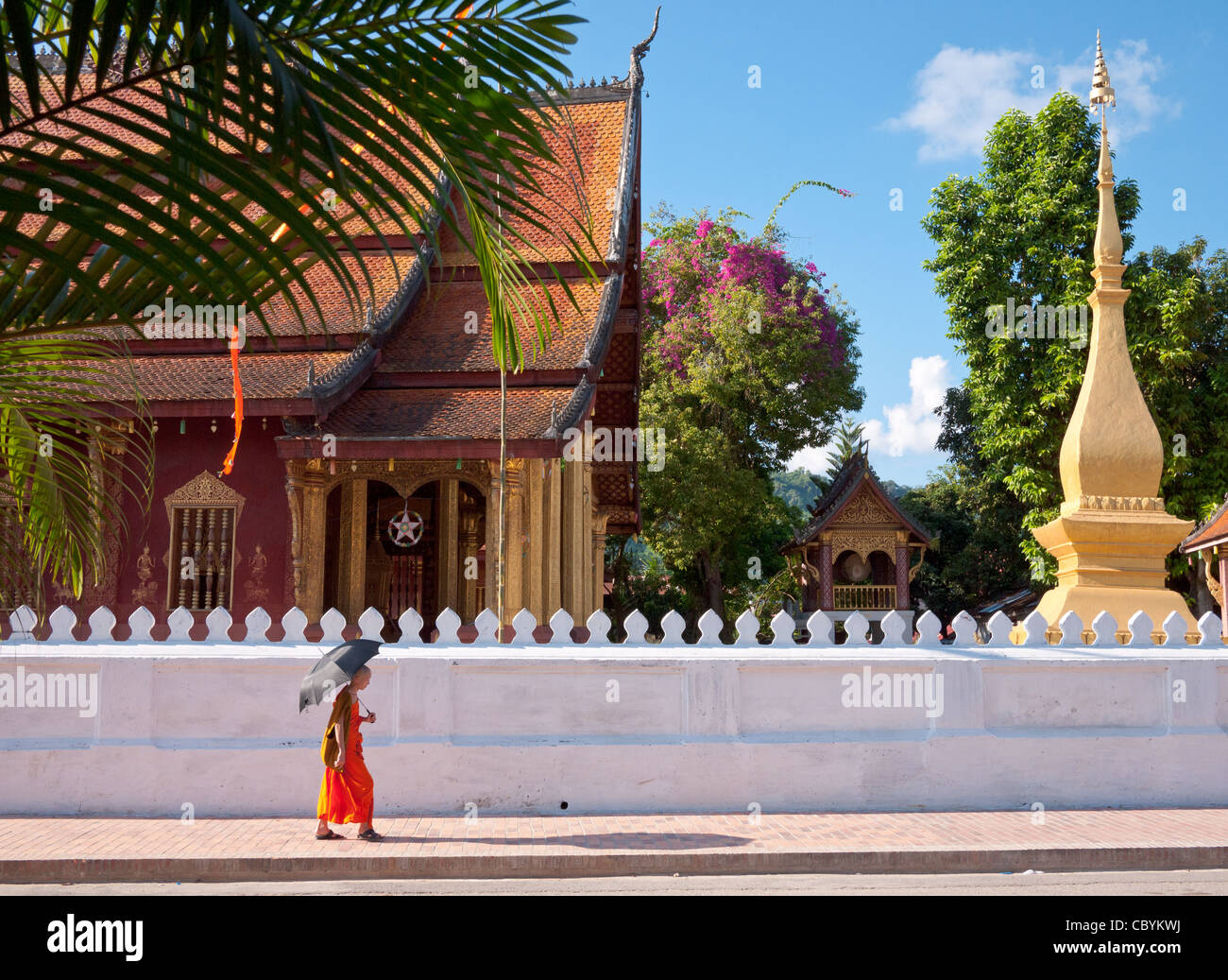 An orange-robed Buddhist monk walks down the street in front of the Wat Sen Temple in Luang Prabang, Laos. - Stock Image
