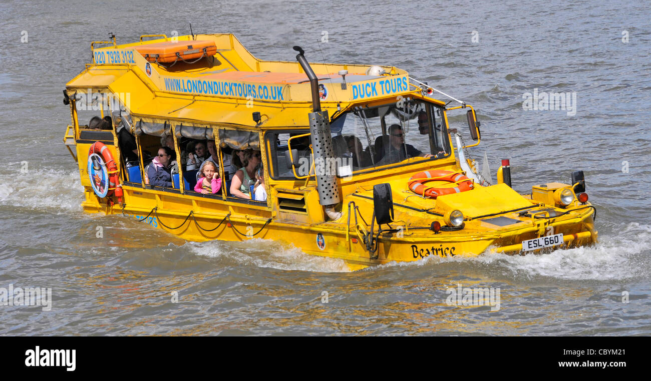Amphibious DUKW modified sightseeing vehicle for tourism & passengers close up of group of people & driver - Stock Image