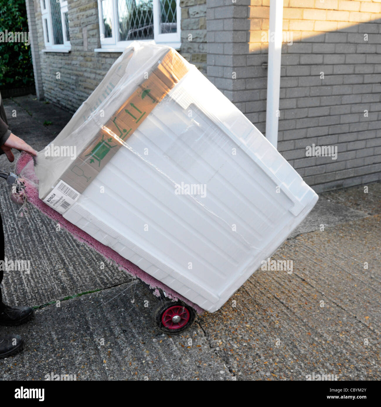 Delivery man using trolley deliver new Bosch tumble dryer from electrical appliance white goods retail supply business - Stock Image