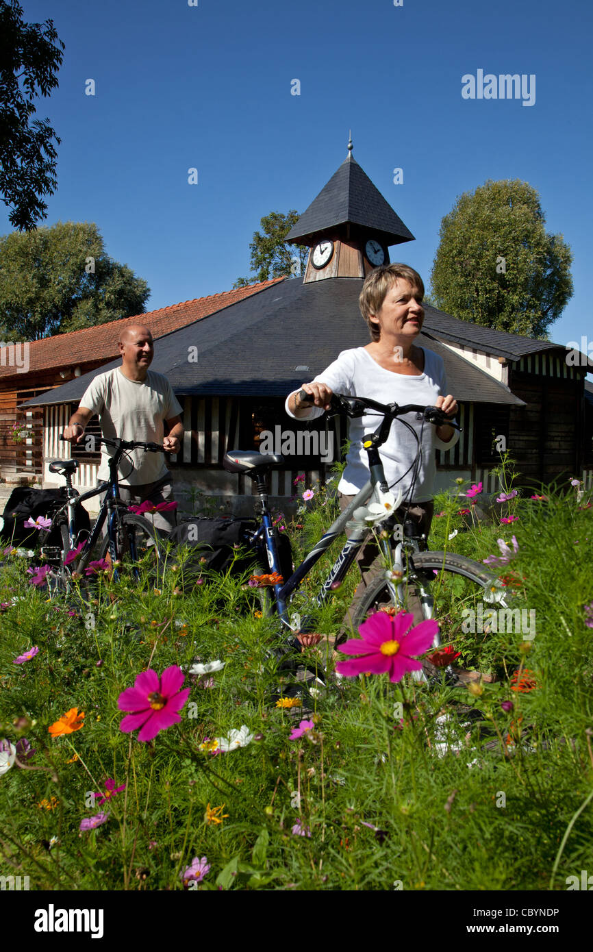 A COUPLE OF CYCLISTS IN FRONT OF THE MILLSTONE AND COBBLESTONE CONSERVATORY, EPERNON, EURE-ET-LOIR (28), CENTRE, - Stock Image
