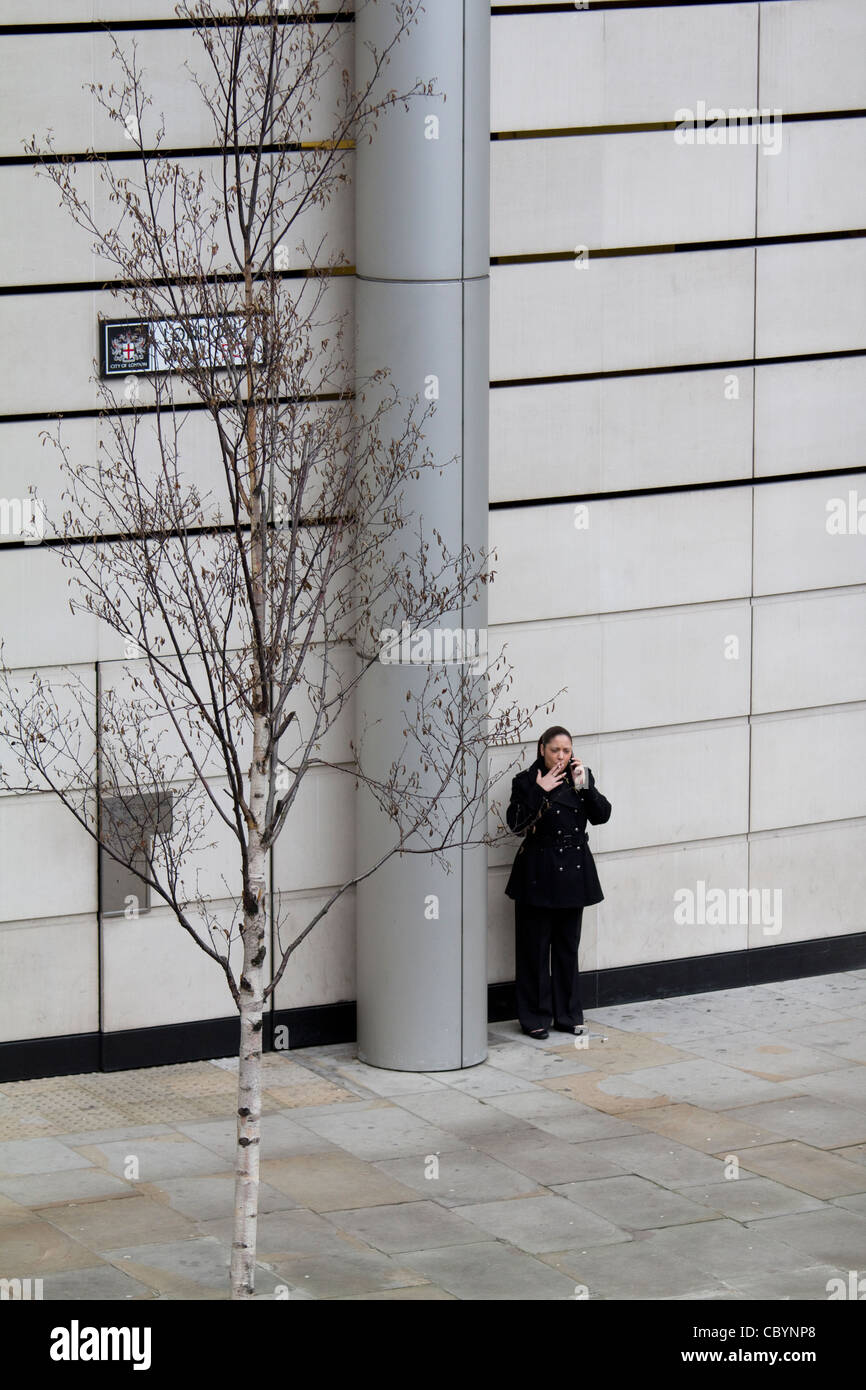 Lone smoker outside office building London Wall, London UK - Stock Image