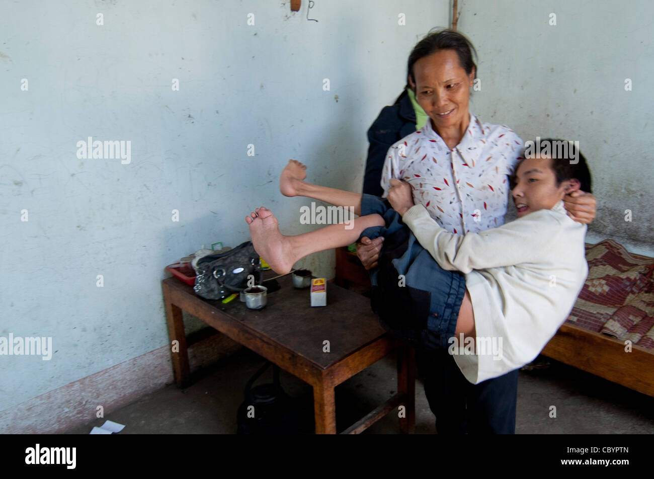 Vietnamese poor mother carrying her disabled child, a handicapped adolescent boy (Vietnam) - Stock Image