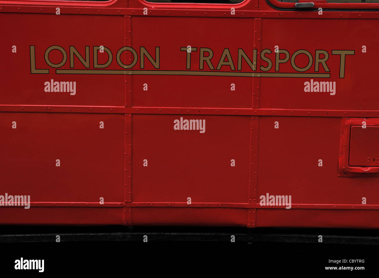 This is the side of a red London Routemaster old bus showing the printing of London transport in gold lettering - Stock Image
