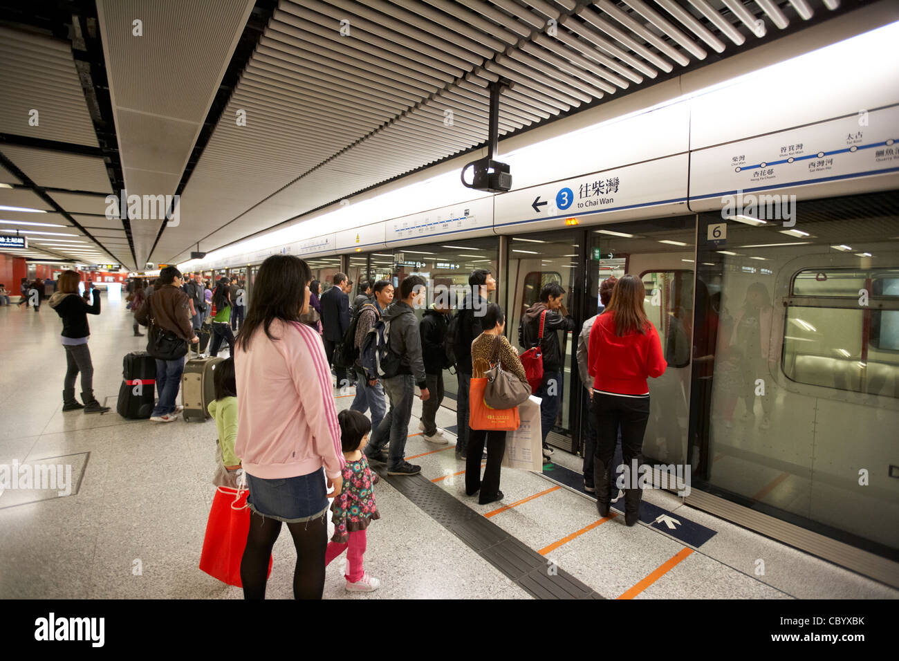 chinese people boarding underground train on hong kong central station mtr public transport system island line hksar - Stock Image