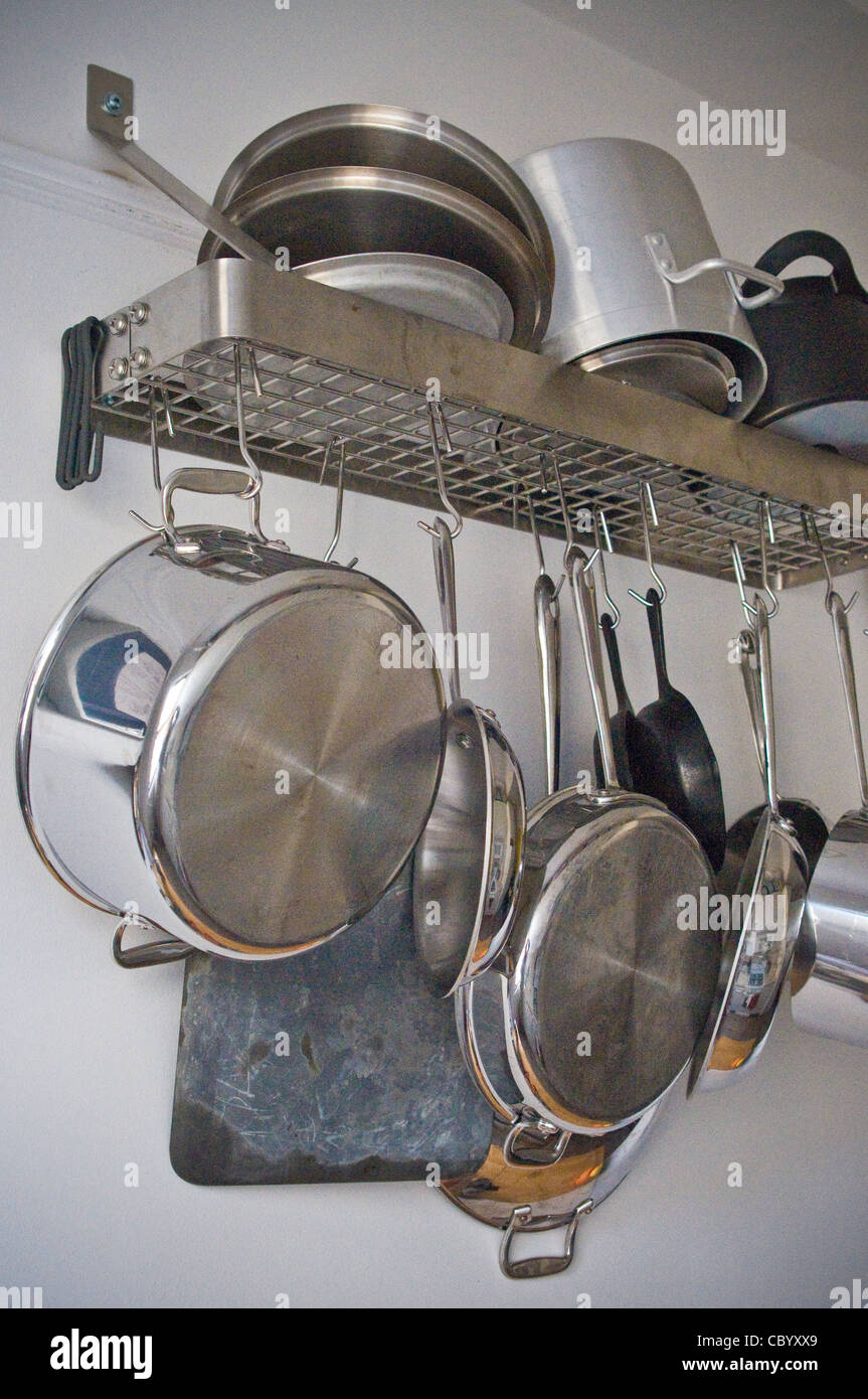 assorted kitchen, pots, pans, utensils, on wall rack, shelf - Stock Image