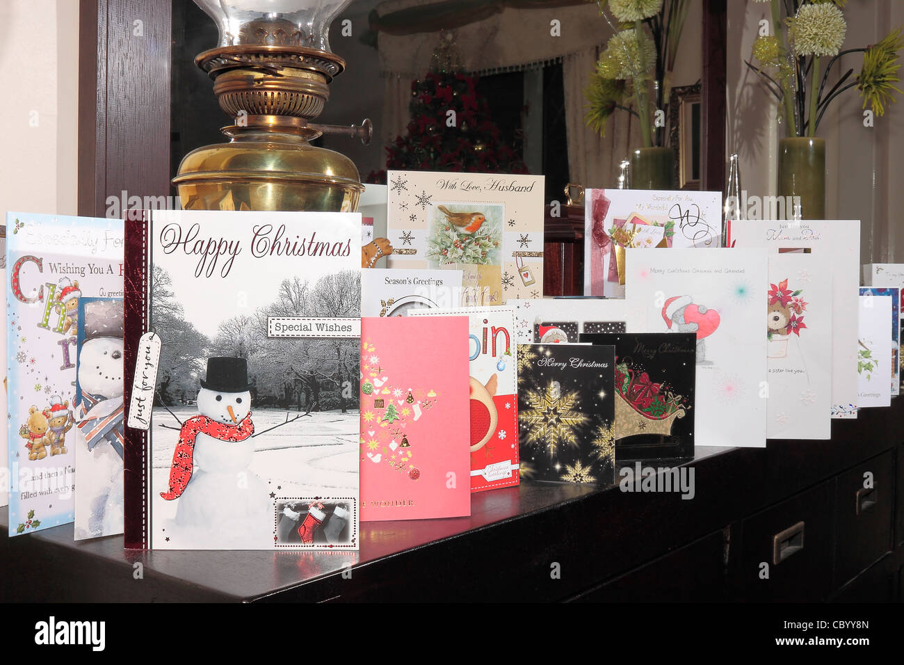 A Line of Christmas Cards on a sideboard with a mirror behind Stock ...