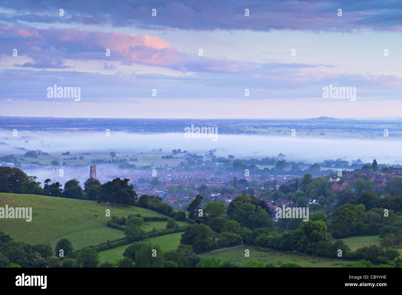 The town of Glastonbury and the Somerset Levels, shrouded in mist, from Glastonbury Tor, in pre-dawn light. - Stock Image