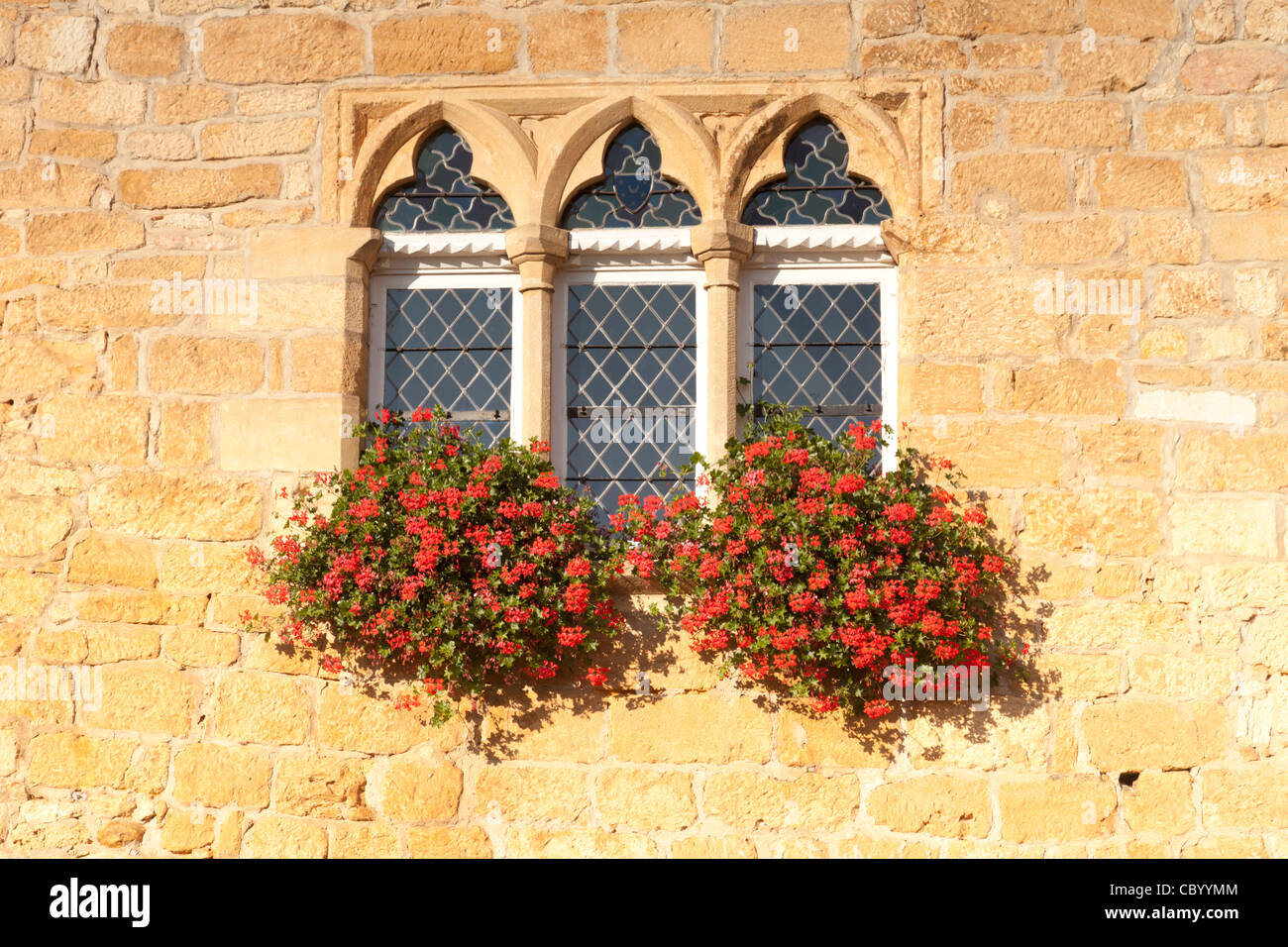 Geraniums in window boxes at the Tourist Information Office in the village of Domme, Aquitaine, France. - Stock Image