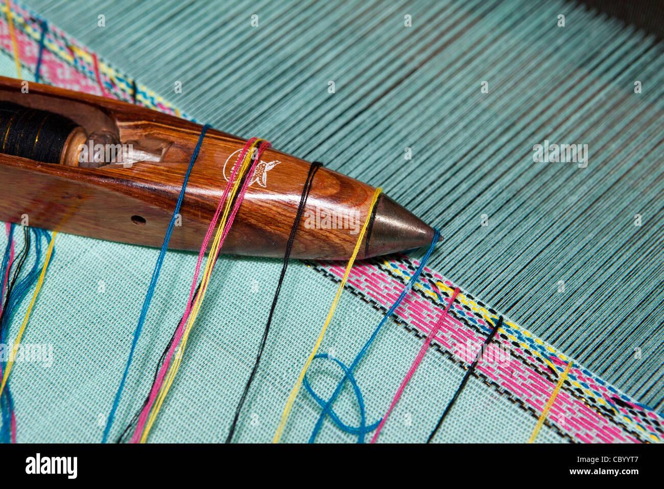 India, Arunachal Pradesh, Along, Paya village, handloom weaving, shuttle and threads on top of cloth being woven - Stock Image