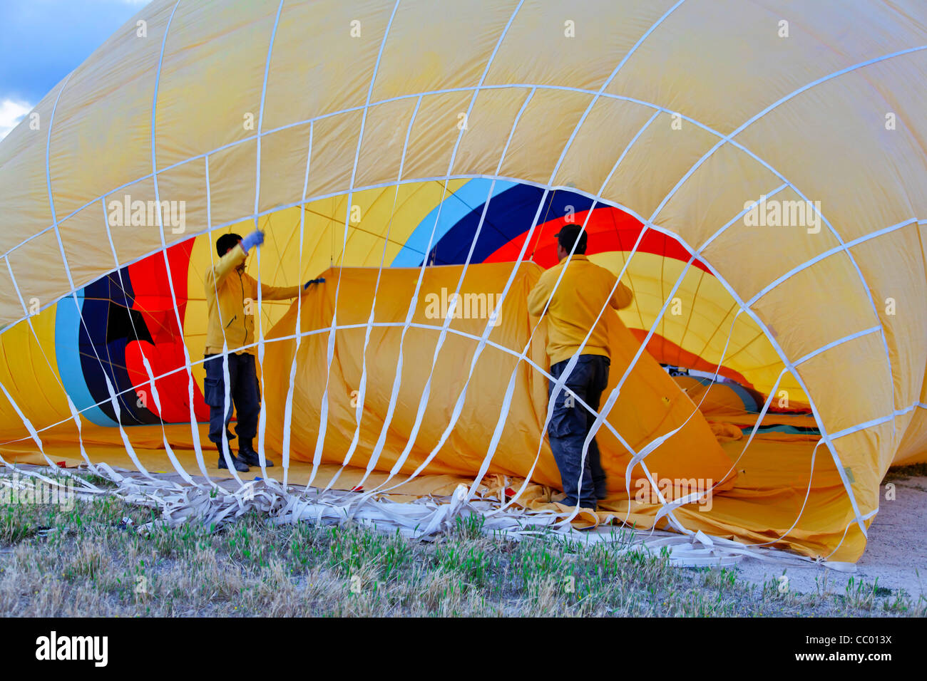 Roadies inside a yellow hot air balloon making ready for flight in Cappadocia Turkey, horizontal landscape with - Stock Image