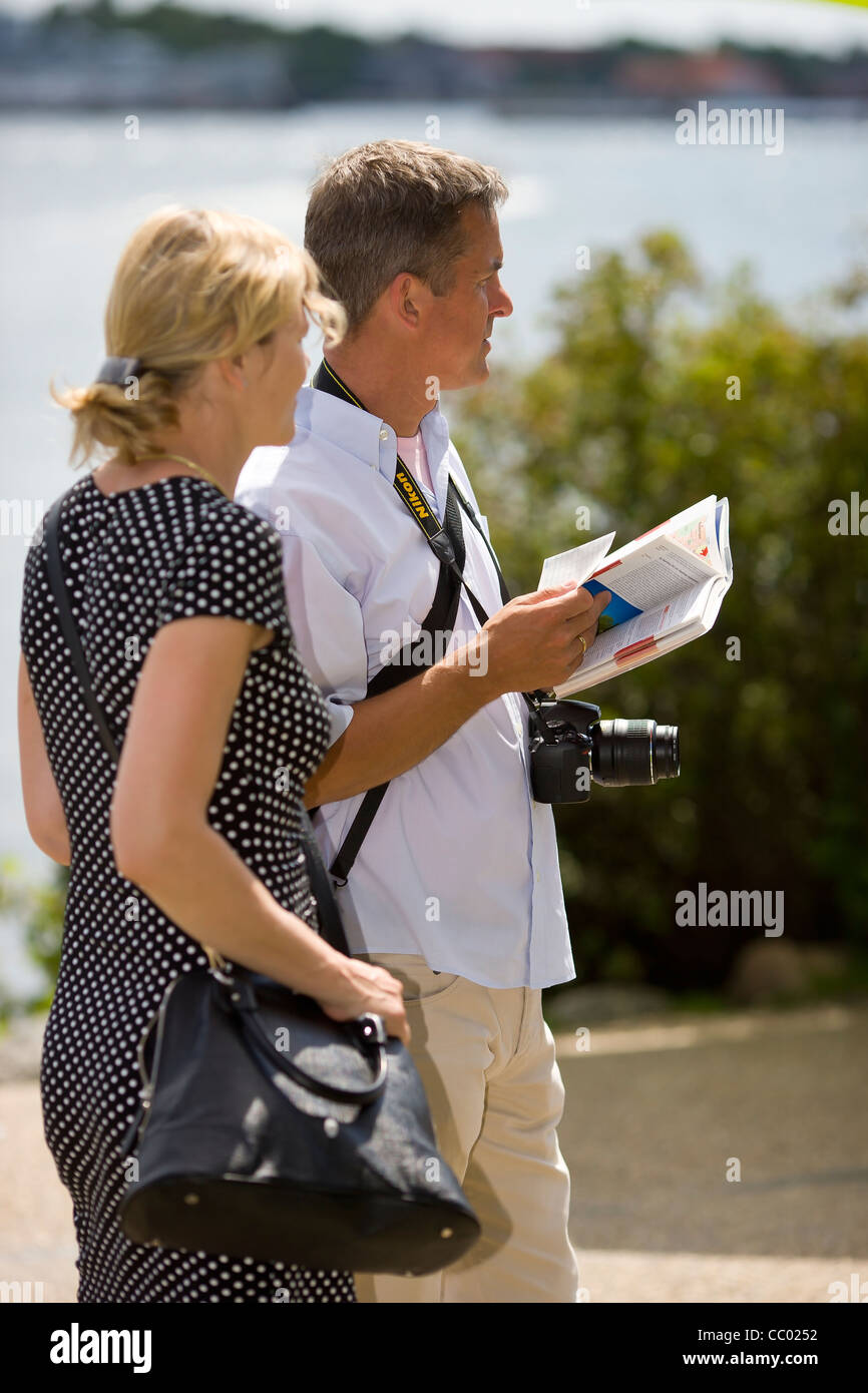Sightseer couple reading a guide book in at the harbour in Copenhagen - Stock Image